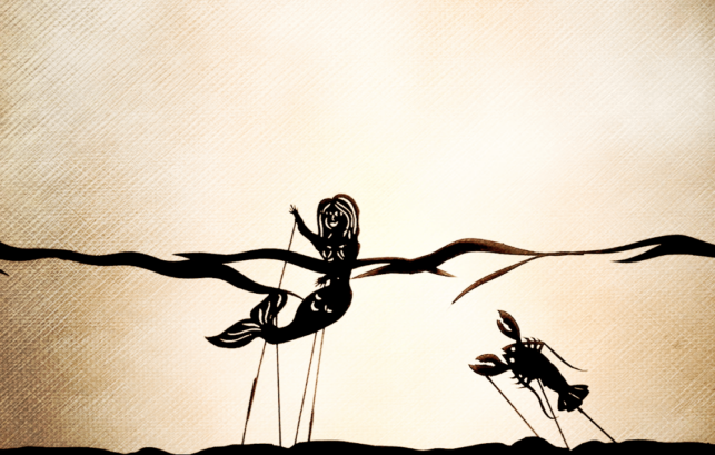 Image shows a shadow puppet show where the image of a mermaid is shown as well as a lobster