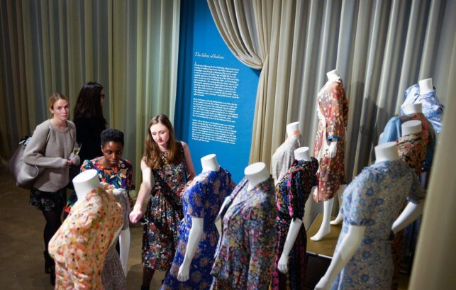 Image of 3 people looking at clothing on display a the Fashion and Textile Museum